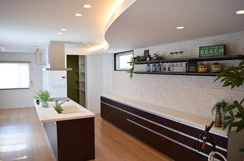 間接照明の下がり天井が帯のようなカーブを描く印象的なキッチン